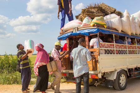 extensively: ZANZIBAR, TANZANIA - CIRCA JULY 2013: People loading cargo and luggage on local public transport vehicle known as Daladala, on July 2013. Daladalas are cheap crowded minibuses that operate extensively on the island.