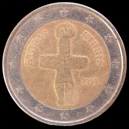 cypriot: National side of two euro coin issued by Cyprus isolated on a black background. The cypriot obverse face depicts a cruciform idol from the chalcolithic period