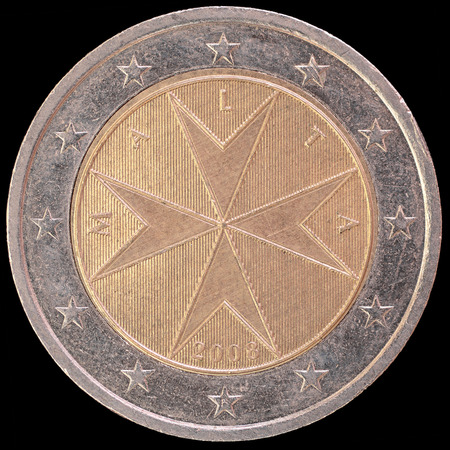 an obverse: National side of two euro coin issued by Malta isolated on a black background. The maltese obverse face depicts the emblem used by the sovereign Order of Malta