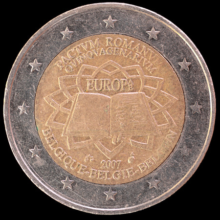 circulated: A commemorative circulated two euro coin issued by Belgium in 2007 celebrating the anniversary of the Treaty of Rome. Image isolated on black backgroun Stock Photo