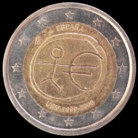 circulated: A commemorative circulated two euro coin issued by Spain in 2009 celebrating the anniversary of Economic and Monetary Union. Image isolated on black background. Stock Photo