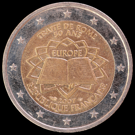 circulated: A commemorative circulated two euro coin issued by France in 2007 celebrating the the anniversary of the Treaty of Rome. Image isolated on black background.