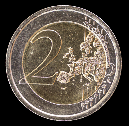 circulated: Common side of two euro coin isolated on a black background. The reverse face displays a map of Europe and was designed by Luc Luycx in 2007 Stock Photo