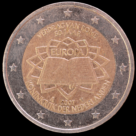 circulated: A commemorative circulated two euro coin issued by Netherlands in 2007 celebrating the anniversary of the Treaty of Rome. Image isolated on black b