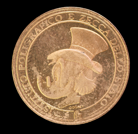 issued: ITALY - CIRCA 1993 - Walt Disney coin depicting the portrait of Uncle Scrooge McDuck issued by Italian mint on 1993. Scrooge McDuck is the Richest Duck in the World as well as a greedy miser. Image isolated on a black background