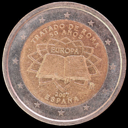 treaty: A commemorative circulated two euro coin issued by Spain in 2007 celebrating the anniversary of the Treaty of Rome. Image isolated on black background. Stock Photo