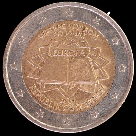 circulated: A commemorative circulated two euro coin issued by Austria in 2007 celebrating the anniversary of the Treaty of Rome. Image isolated on black background. Stock Photo