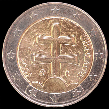 double cross: National side of two euro coin issued by Slovakia isolated on a black background. The slovak obverse face depicts the national emblem, a double cross on three hills