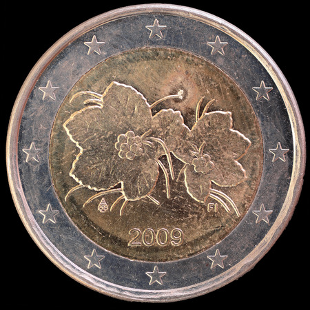 an obverse: National side of two euro coin issued by Finland isolated on a black background. The finnish obverse face depicts cloudberries and cloudberry flowers Stock Photo