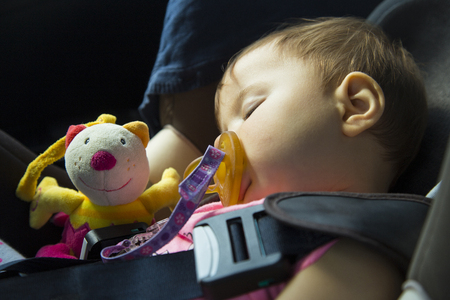 9 months old baby girl sleeping in the car seat with her puppet Stock Photo