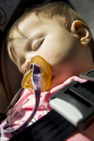 9 months: 9 months old baby girl sleeping in the child car seat Stock Photo