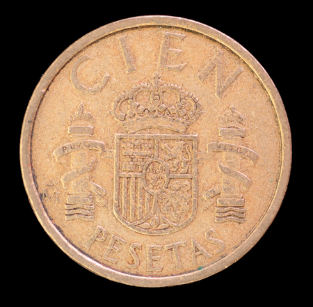 issued: The tail face of 100 pesetas coin, issued by Spain in 1984, depicting the national coat of arms. Image isolated on black background Stock Photo