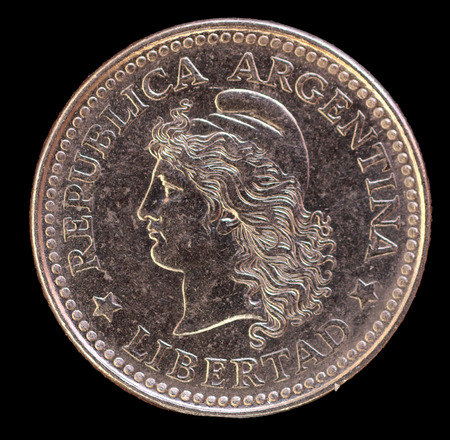 issued: The head face of 10 centavos coin, issued by Argentina il in 1959, depicting the portrait of the capped liberty head. Image isolated on black background