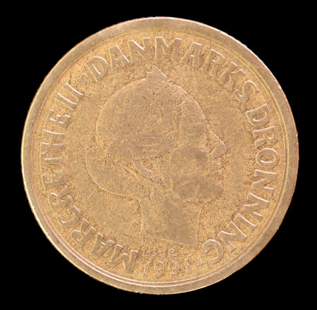 issued: The head face of 20 krone coin, issued by Denmark in 1991, depicting a portrait of Queen Margrethe II. Image isolated on black background