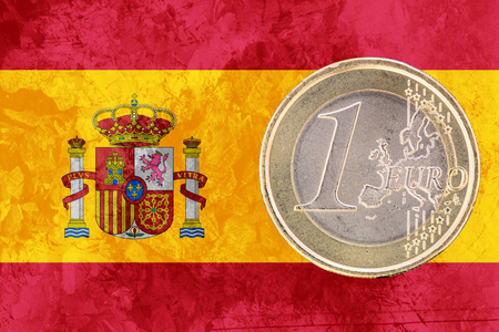 circulated: Common face of one euro coin from Spain isolated on the national spanish flag as background