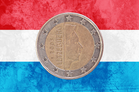 circulated: Two euros coin from Luxembourg isolated on the national luxembourgish flag as background