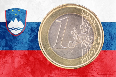 circulated: Common face of one euro coin from Slovenia isolated on the national slovene flag as background
