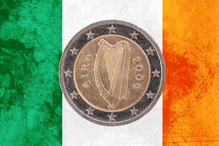 Two euros coin from Ireland isolated on the national irish flag as background Stock Photo