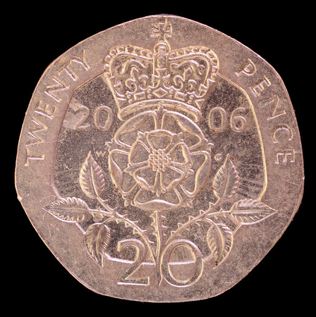 issued: The tail face of twenty pence coin, issued by United Kingdom in 2006, depicting the royal emblem. Image isolated on black background