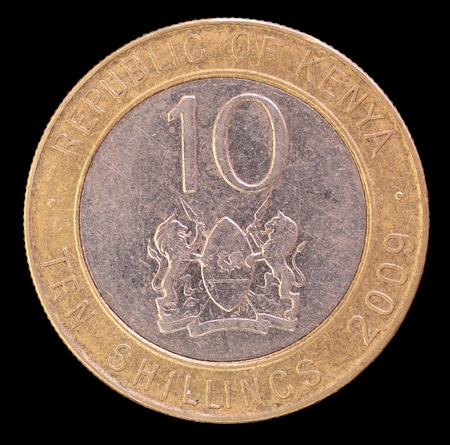 issued: The tail face of ten shillings coin, issued by Kenya in 2009, depicting the lions and the shield, symbol of the country. Image isolated on black background