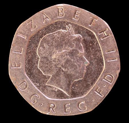 issued: The head face of twenty pence coin, issued by United Kingdom in 2006, depicting the portrait of Queen Elizabeth. Image isolated on black background Stock Photo