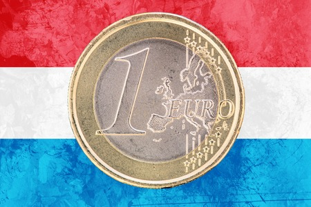circulated: Common face of one euro coin from Luxembourg isolated on the national luxembourgish flag as background
