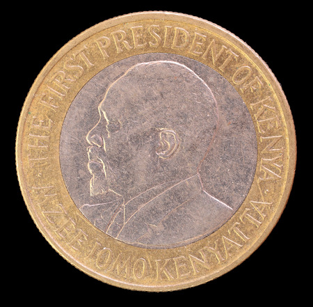 issued: The head face of ten shillings coin, issued by Kenya in 2009, depicting the portrait of the First President Jomo Kenyatta. Image isolated on black background Stock Photo