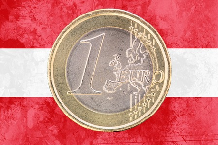 circulated: Common face of one euro coin from Austria isolated on the national austrian flag as background