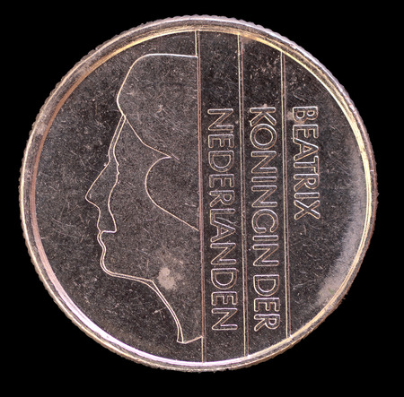 25 cents: The head face of 25 cents of guilder coin, issued by Netherlands in 1985, depicting the portrait of the Princess Beatrix. Image isolated on black background