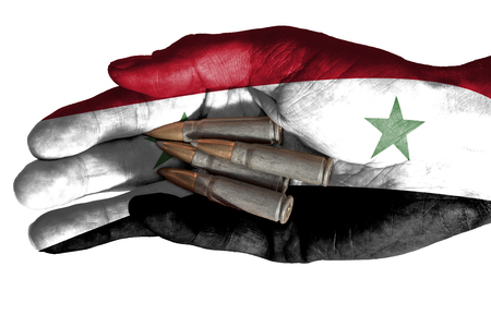 Flag of Iraq overlaid the hand of an adult man holding four bullets. Conceptual image for war, violence, conflicts. Image isolated on white background