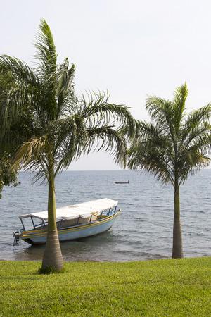 touristic: Floating touristic boat near bright coast with windy palms. Lake Victoria, Tanzania