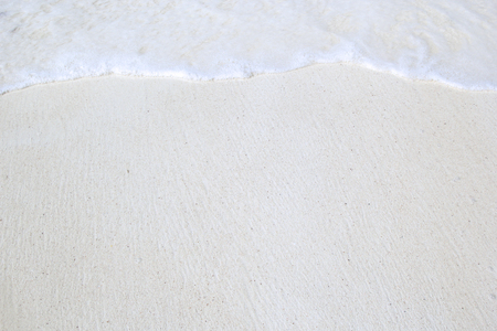 white sand beach: White tropical beach with waves in sunlight. Can be used as texture or background. Stock Photo