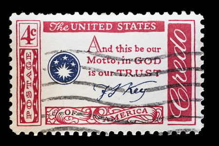 credo: UNITED STATES OF AMERICA - CIRCA 1960: A used postage stamp printed in United States shows the famous statement: And this be our Motto, in GOD is our trust, circa 1960