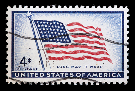 used stamp: UNITED STATES OF AMERICA - CIRCA 1957: A used postage stamp printed in United States shows a flapping Flag of USA, circa 1957