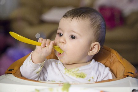 dirty clothes: Cute six months old baby eating with spoon with very dirty clothes Stock Photo