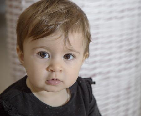 ojos marrones: Retrato de un a�o de edad del beb� con los ojos marrones que miran a la c�mara con calma Foto de archivo