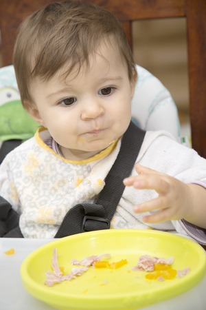 eyes looking down: Portrait of cute one year old baby with dirty shirt eating with hands Stock Photo