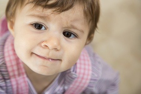 멀리 슬프게도 바라 보는 갈색 눈을 가진 귀여운 한 살짜리 아이의 근접