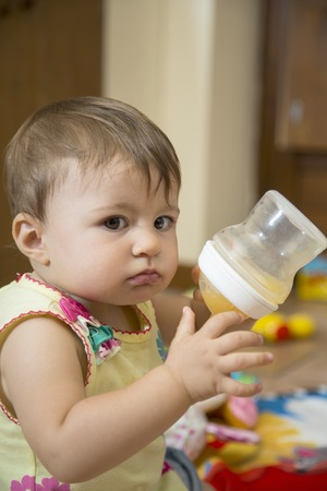 feeding bottle: Portrait of cute one year old baby girl looking at camera and holding a feeding bottle