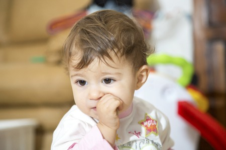 one year: Cute one year old baby with finger in mouth looking away