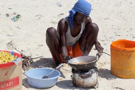 disadvantaged: ZANZIBAR, TANZANIA - JUNE 21: a man cooks on the beach with a simple makeshift kitchen on June 21, 2013 in Zanzibar