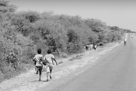 mwanza: MWANZA, TANZANIA - JUNE 11: boys running along the road on June 11, 2013 in Mwanza. Education is a leading cause of poverty since in Tanzania school is not free and many children cannot attend studies