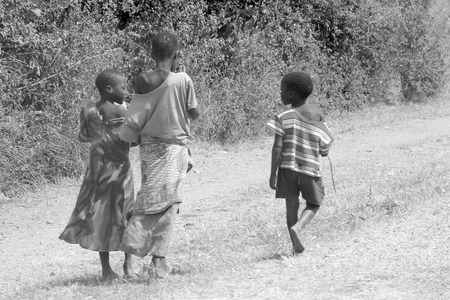 MWANZA, TANZANIA - JUNE 11: a group of children along a road on June 11, 2013 in Mwanza. In rural settings of Tanzania many children live in extreme poverty or are orphans due to HIV. Editorial