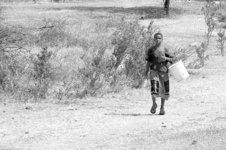 safe water: MWANZA, TANZANIA - JUNE 11: a young girl brings an empty bucket on June 11, 2013 in Mwanza. The scarcity of water is a serious issue in Tanzania, since one third of the country is arid to semi-arid Editorial