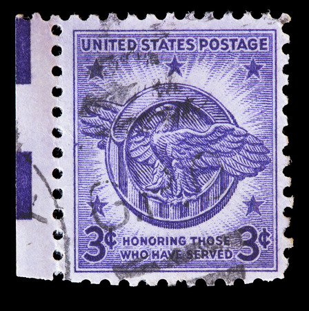 commemorate: UNITED STATES OF AMERICA - CIRCA 1946: A used postage stamp printed in United States shows the eagle national emblem on violet to commemorate the veterans of World War II circa 1946