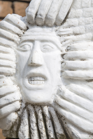 nightmarish: Close-up of the carved face of a man with gritted teeth in a white wall. Several hands are clawing the face. Conceptual image for fear, nightmare, aggression