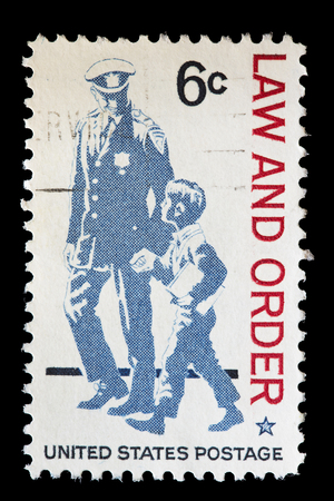 used stamp: UNITED STATES OF AMERICA - CIRCA 1968: A used postage stamp printed in United States shows a policeman helping a boy and the text Law and Order, circa 1968 Editorial