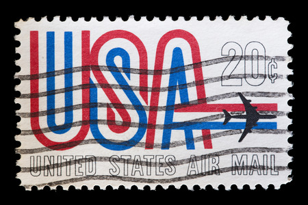 UNITED STATES OF AMERICA - CIRCA 1968: A used airmail postage stamp printed in United States shows an airplane flying over the word USA with national flag colors, circa 1968