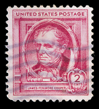used stamp: UNITED STATES OF AMERICA - CIRCA 1940: A used postage stamp printed in United States shows portrait of the writer James Fenimore Cooper on red background, circa 1940