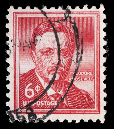 theodore roosevelt: UNITED STATES OF AMERICA - CIRCA 1954: A used postage stamp printed in United States shows a portrait of the President Theodore Roosevelt on red background, circa 1954